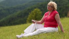 Woman sits on a green grass and and listens to music Stock Footage