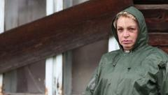 Woman in green raincoat stands near uninhabited house Stock Footage