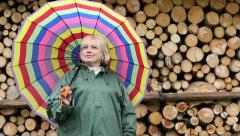Woman in green slicker stands near lumber and smiling Stock Footage