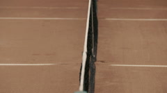 Yellow-green tennis ball stuck in the grid on red clay courts. Stock Footage