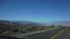 HIGHWAY, driving by desert mountains, blue sky Stock Footage