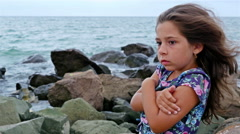 Sorrowful little girl standing alone on the rocks by the stormy sea Stock Footage