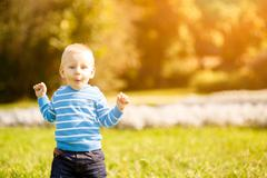 little boy standing in grass - stock photo