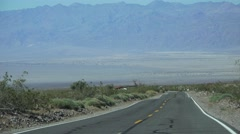 HIGHWAY, driving by desert mountains, tow truck removing car Stock Footage