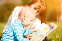Woman with son sitting and read fairytale Stock Photos