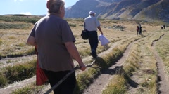 Senior people hiking picturesque Bulgarian mountains along a of Rila Lake shore Stock Footage