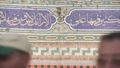 Islamic worshippers pass tiled wall at mosque in Amman, Jordan Stock Footage