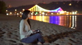 The woman sit on the beach, hold tablet and watch away by picturesque embankment Footage