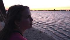 Female looking out into ocean sunset at night Stock Footage