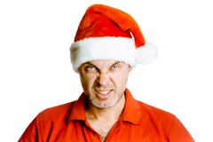 Unshaven angry man in a red shirt and Santa hats. Studio. isolated - stock photo