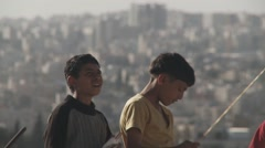 Young children fly kites in refugee camp, Amman, Jordan Stock Footage