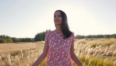 Happy girl walking alone in autumn golden field. Relaxed, freedom and satisfied - stock footage