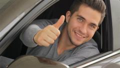 Young man doing thumps-up in car - stock footage
