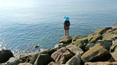 Young woman in summer dress and blue hat relaxing on the rocks on the sea shore Stock Footage