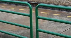 Green metal fence and yellow dash line - stock photo
