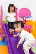 Asian Chinese little sister and brother playing on the slide - stock photo
