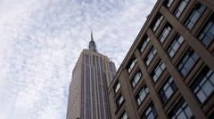 Upward angle street view driving landmark skyscraper Empire State Building NYC Stock Footage