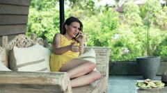 Angry woman talking on cellphone while lying on sofa on terrace Stock Footage
