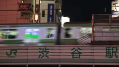 JR Train passing on elevated track in Shibuya district at night, Tokyo, Japan Stock Footage