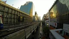 Bangkok's BTS train leaving station in evening sunlight. Stock Footage