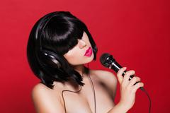 Stylish girl singing with a mike, red background Kuvituskuvat