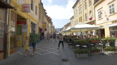 Three old women passing by an outdoor restaurant in Republicii street, Brasov Stock Footage