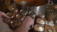 Man inspects mason jar lids then picks up case Stock Footage