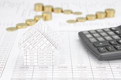 House with calculator have blur step of gold coins Stock Photos