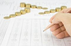 Man holding pencil for audit have blur step gold coins - stock photo
