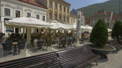 Benches, small trees and outdoor restaurants in the Council Square, Brasov Stock Footage