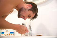 Man washes in bathroom - stock photo