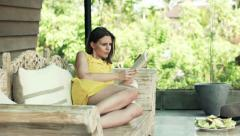 Pretty, young woman reading book lying on sofa on terrace Stock Footage