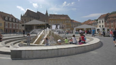 People resting and children playing at the fountain in Council Square, Brasov Stock Footage