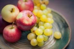 Plate with fresh autumnal fruits. apples in selective focus Stock Photos