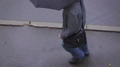 Rainy day, man walking under umbrella, overhead view, slow motion. Stock Footage