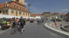 People resting on benches near the fountain at the Council Square, Brasov Stock Footage