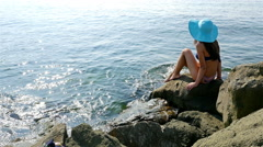 Young woman in swimming suit and blue hat sitting on rocks on the sea shore - stock footage