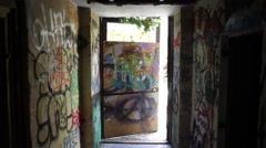 Exit door from an abandoned scary building, graffiti everywhere - stock footage
