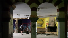2 Men take photographs inside an abandoned building, graffiti on the walls - stock footage