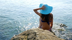 Young woman in swimming suit and blue hat sitting on rocks on the sea shore Stock Footage