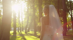 Bride is throwing a flower bouquet at wedding in a sunny park - stock footage