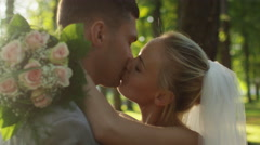Young bride and groom are kissing in a sunny park Stock Footage