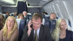 Annoying passenger on plane speaking loudly on phone - stock footage