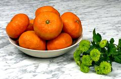 Tangerines on a plate with green gerber on a marble table Stock Photos