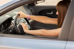 woman driving a car with hand on horn button - stock photo