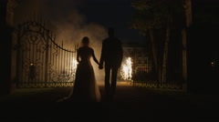 Happy young newlyweds are walking through fireworks in a park in the evening - stock footage