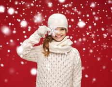 Smiling girl in winter clothes with big snowflake Stock Photos