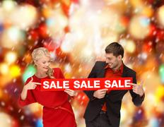Stock Photo of smiling woman and man with red sale sign
