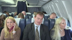 Aircraft passengers annoyed by mobile phone call Stock Footage