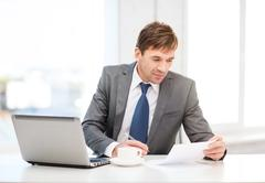 Stock Photo of businessman with laptop computer and documents